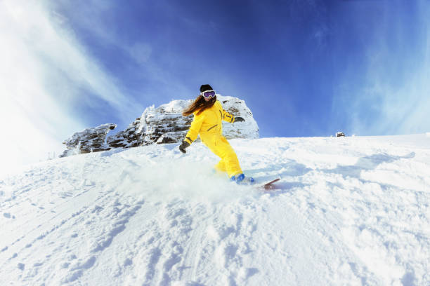 Girl snowboarder backcountry fast snowboarding Girl snowboarder moving fast from off-piste slope. Backcountry ski and snowboard resort Sheregesh. ski holiday stock pictures, royalty-free photos & images
