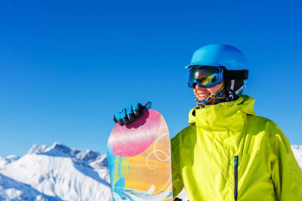 Girl snowboarder having fun in the winter ski resort. stock photo