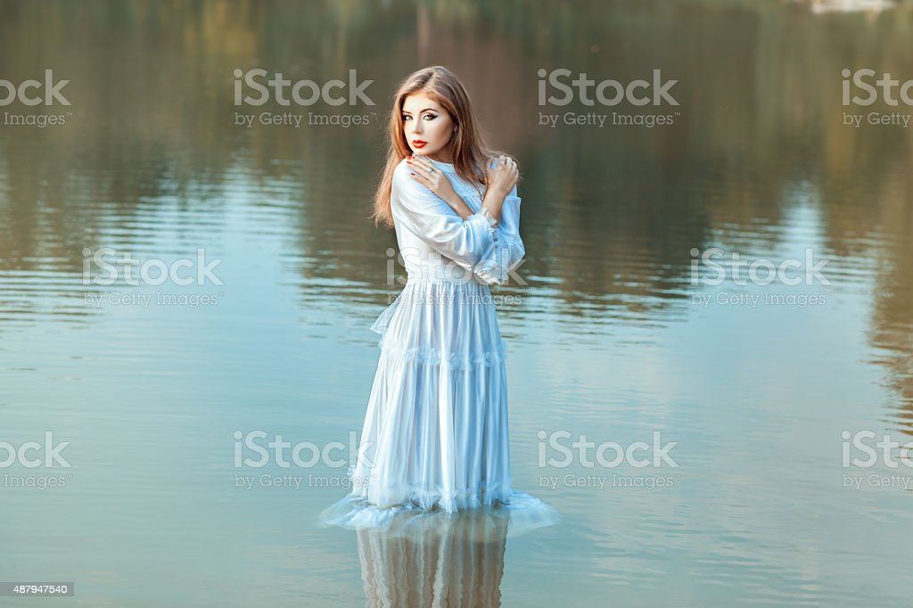 Girl soaked clothes in the lake water. stock photo