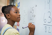Portrait of african girl writing solution of sums on white board at school. Black schoolgirl solving addition sum on white board with marker pen. School child thinking while doing mathematics problem.