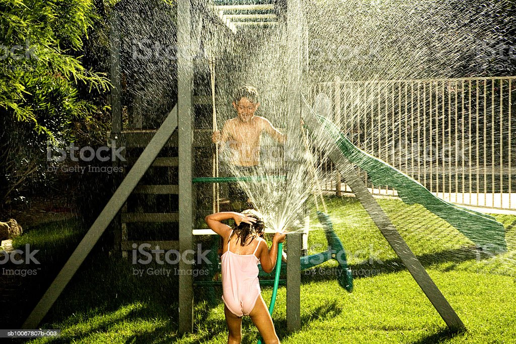 Girl (4-5) spraying water on boy (8-9) with hose royalty free stockfoto