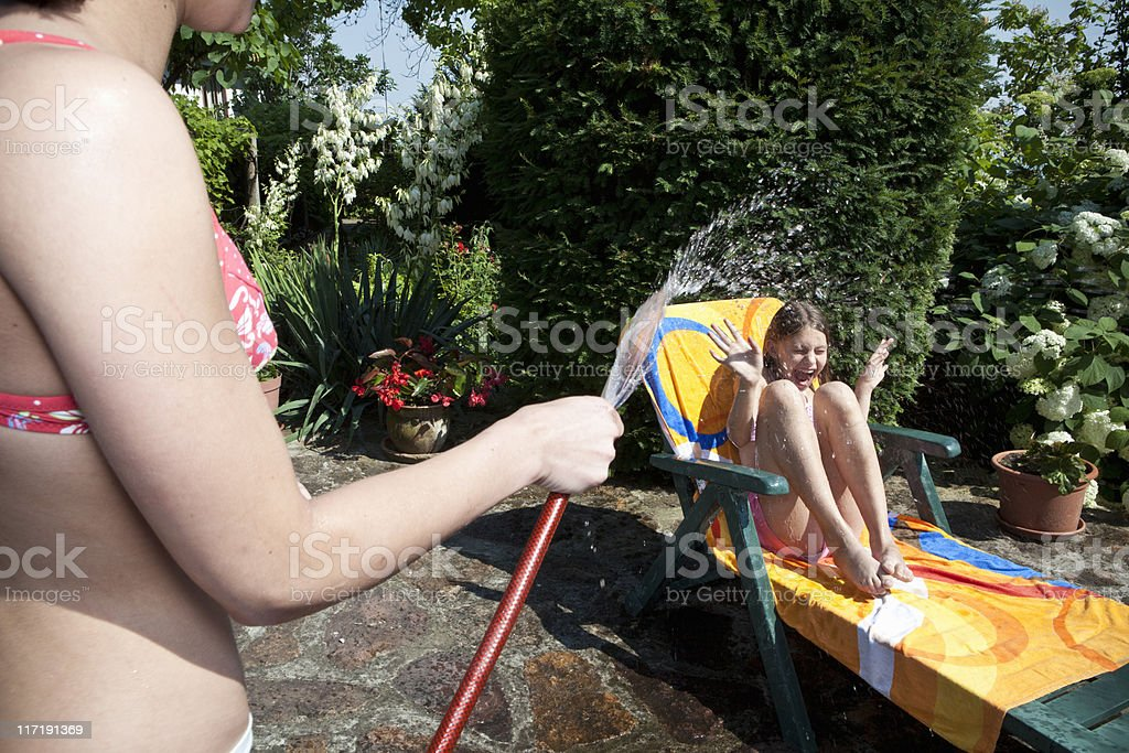 Girl sprays water on sister stock photo