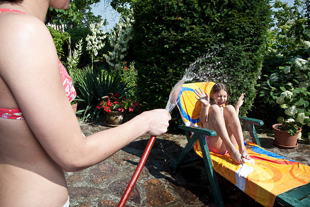 Girl sprays water on sister stock photo