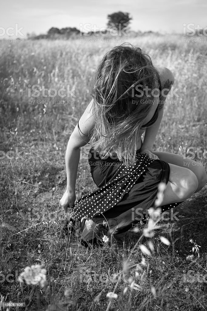 Girl squatting in countryside stock photo