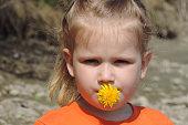 girl squinting holds yellow dandelion flower in her lips