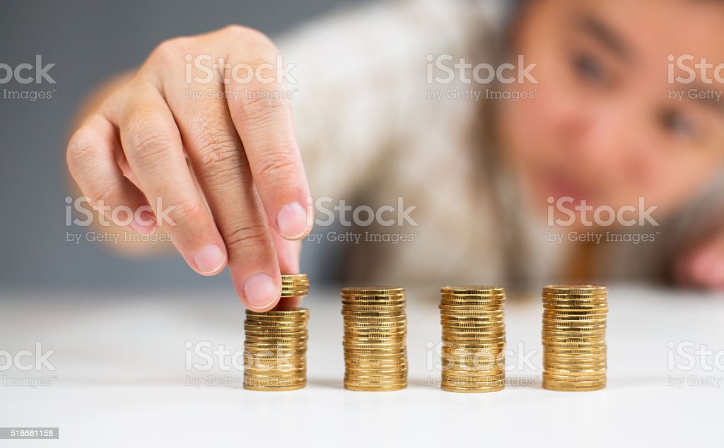 girl stacking coins stock photo