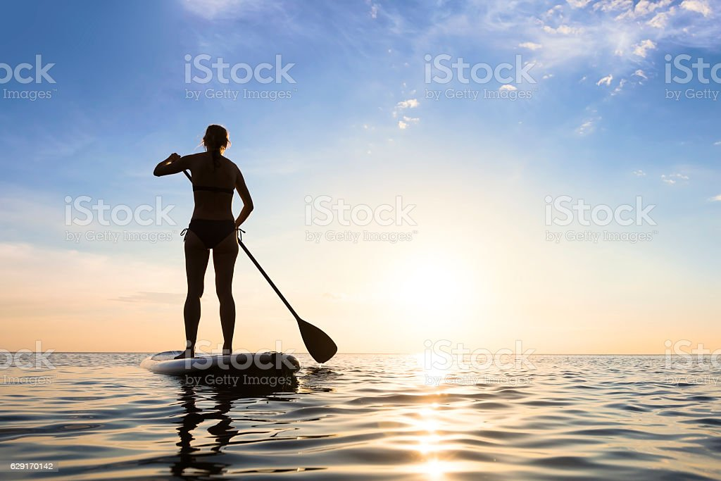 Girl stand up paddle boarding (sup) on quiet sea, sunset stock photo