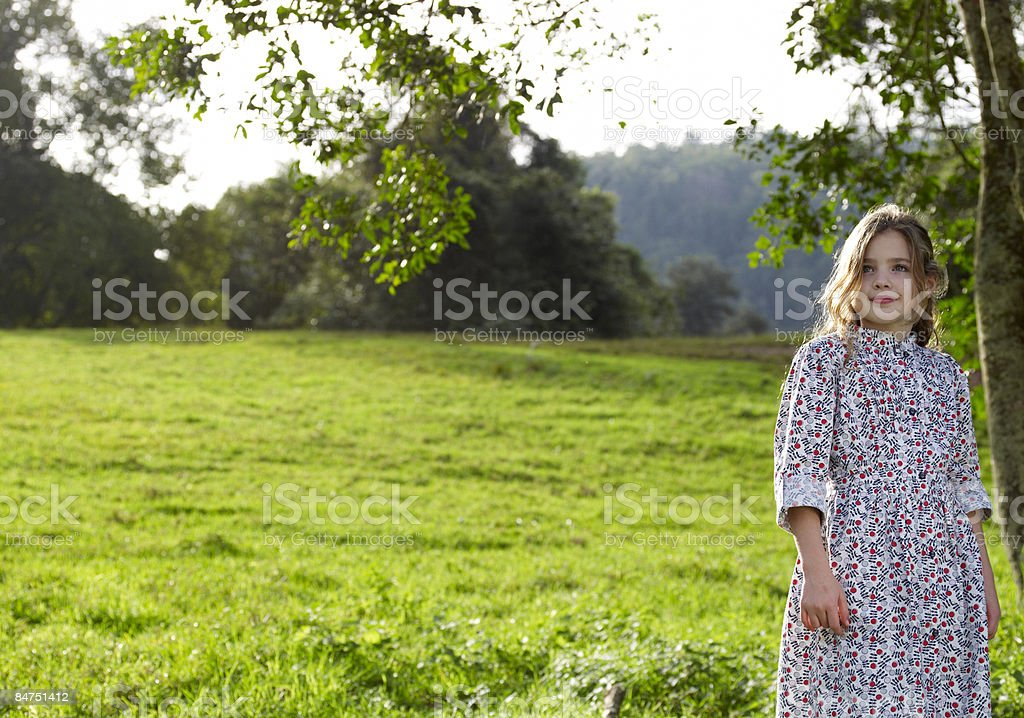 Girl standing alone outdoors in green field royalty-free stock photo