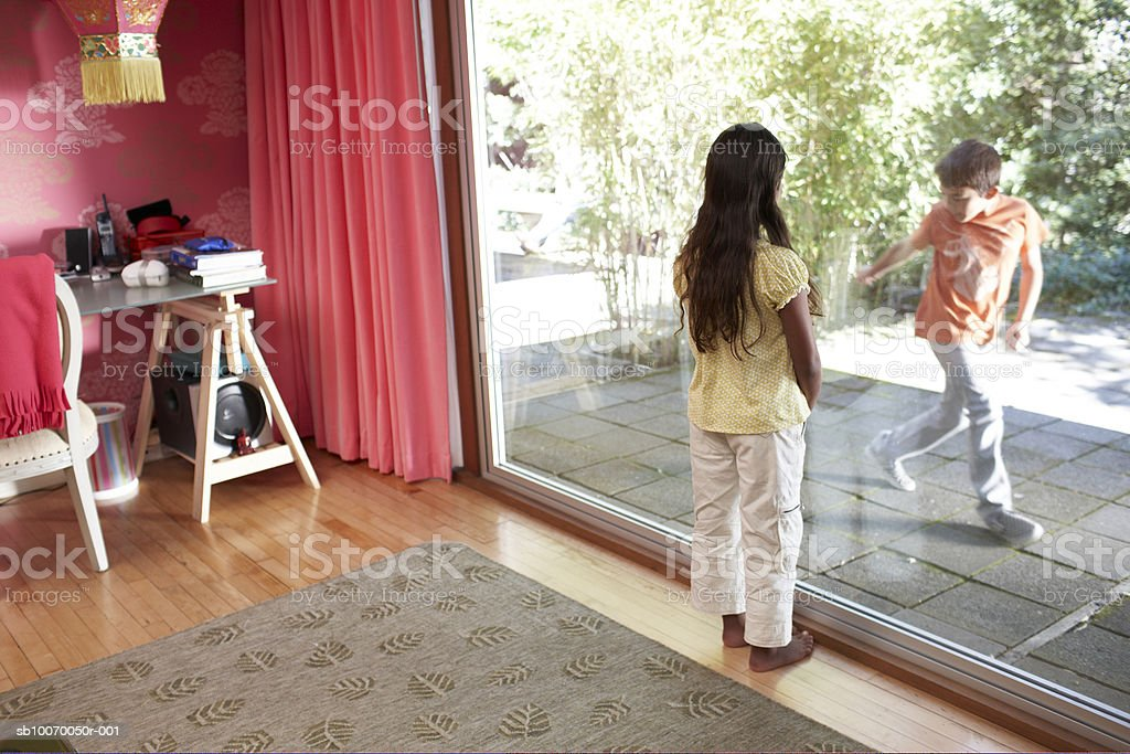 Girl (6-11) standing and looking at boy through window royalty-free stock photo