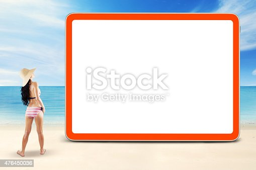 istock Girl standing at coast near the empty board 476450036