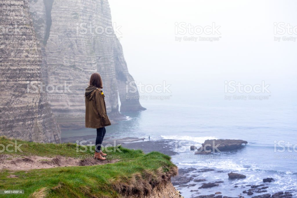 girl standing at the edge of rock in the Etretat royalty-free stock photo
