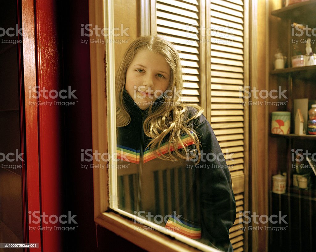 Girl (12-13) standing behind glass door, portrait foto de stock libre de derechos