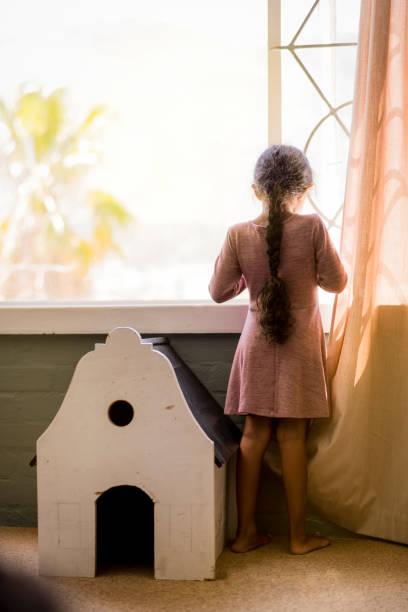 mädchen stehen von puppenhaus gegen fenster zu hause traurig. - mädchenraum vorhänge stock-fotos und bilder