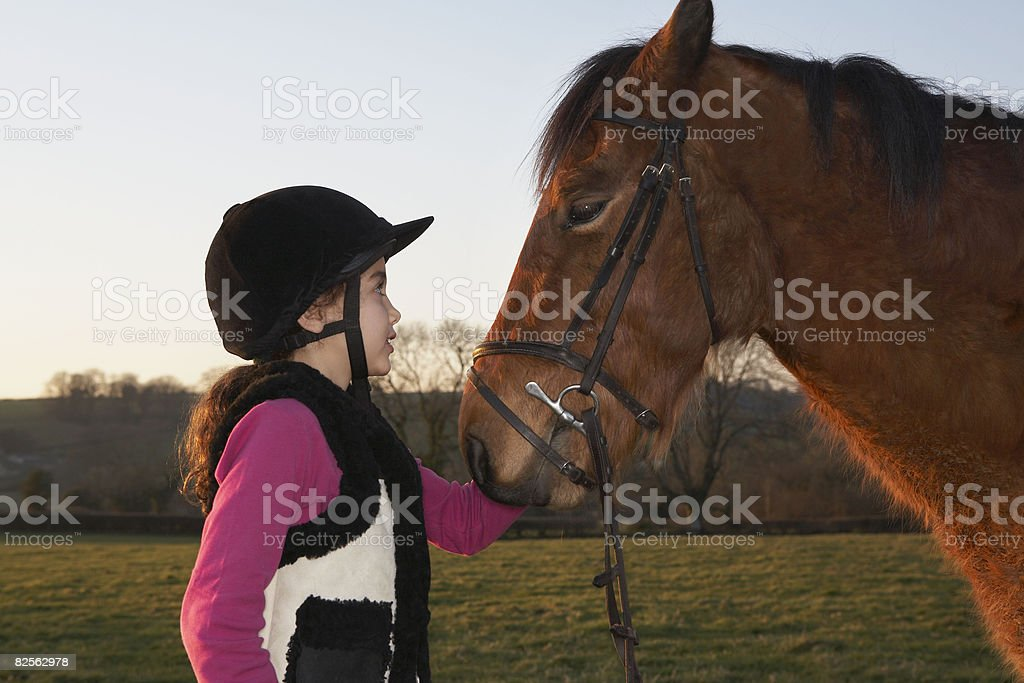Girl standing by pony stock photo