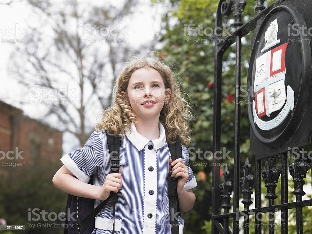 Girl Standing By School Gate stock photo