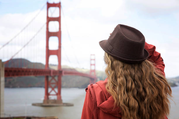 A girl standing by the Golden Gate Bridge A girl holding onto her hat on a windy day jude beck stock pictures, royalty-free photos & images