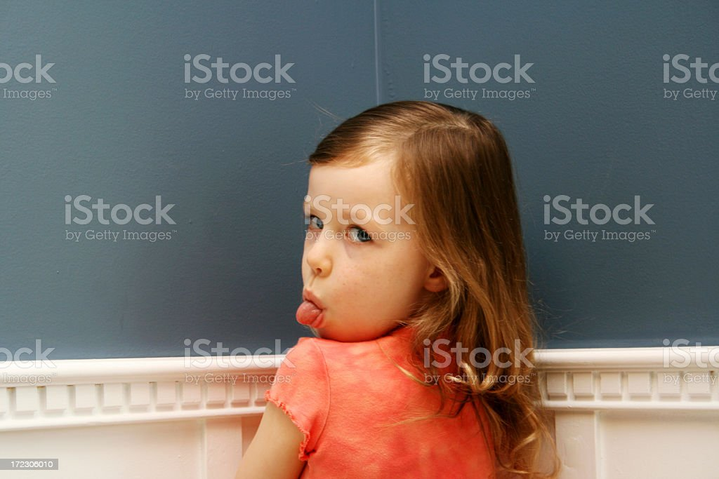Girl standing in corner with tongue stuck out for time out stock photo