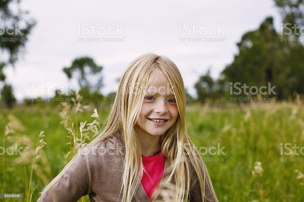 Girl standing in field royalty free stockfoto