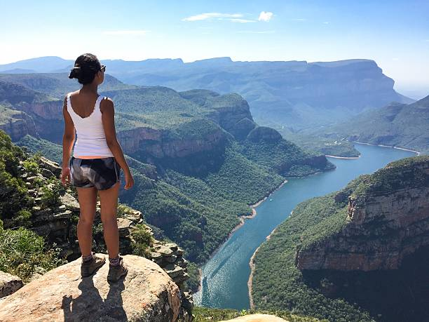 Girl standing in front of a canyon stock photo