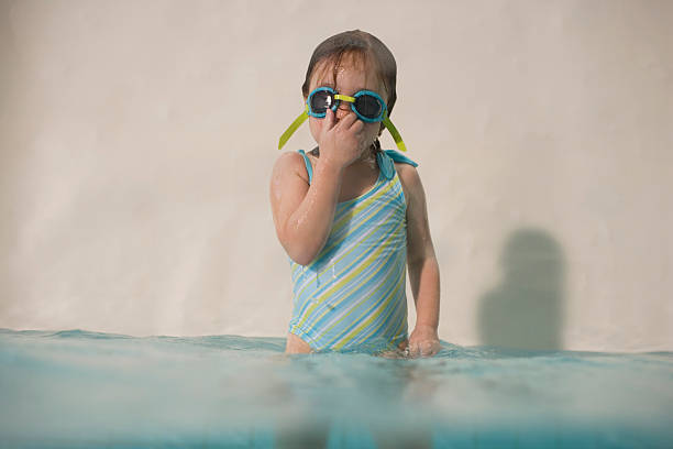 Girl (3-5) standing in swimming pool, wearing goggles and holdin stock photo