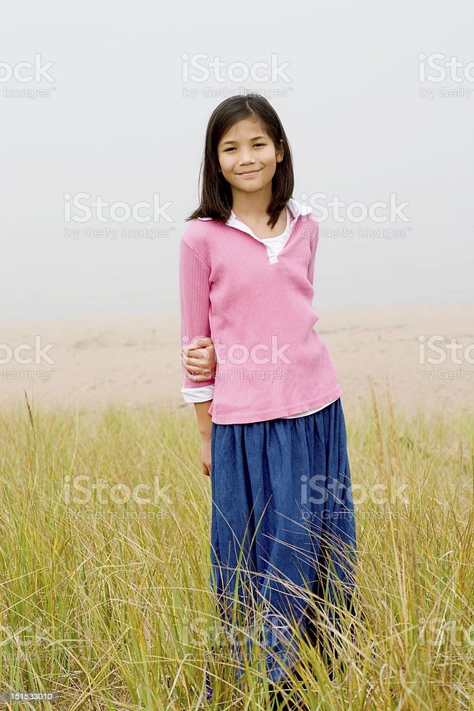 Girl standing in tall grassy field royalty-free stock photo