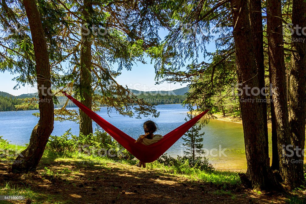 girl standing in the hammock and rest stock photo