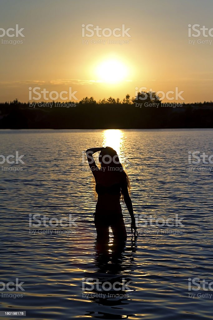 girl standing in the lake at sunset royalty-free stock photo
