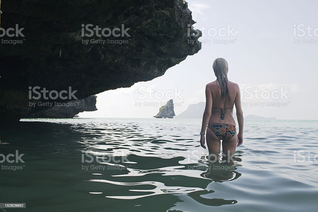Girl standing in water under rocks stock photo