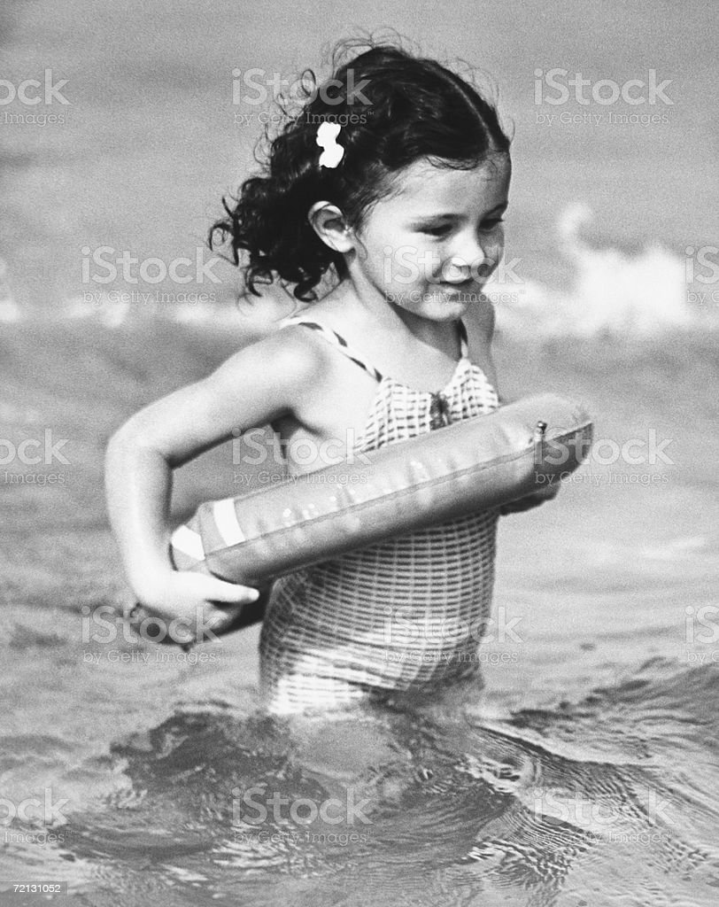 Girl (4-5) standing in water with inflatable ring (B&W) royalty-free stock photo