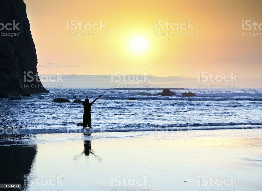 Girl standing in waves, arms raised to sky at sunset royalty-free stock photo