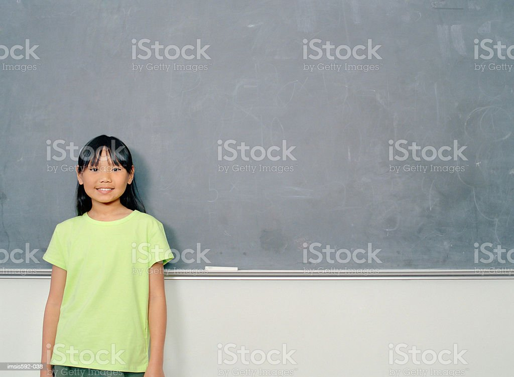 Girl standing near blackboard royalty-free stock photo