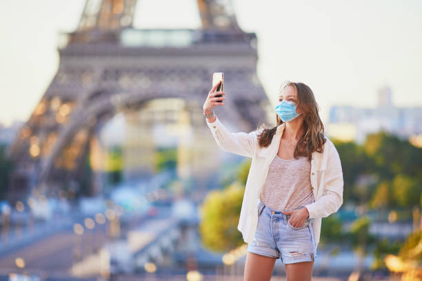 Girl standing near the Eiffel tower in Paris and wearing protective face mask during coronavirus outbreak stock photo