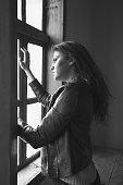 Beautifu girl looking thoughtful while looking through a window.