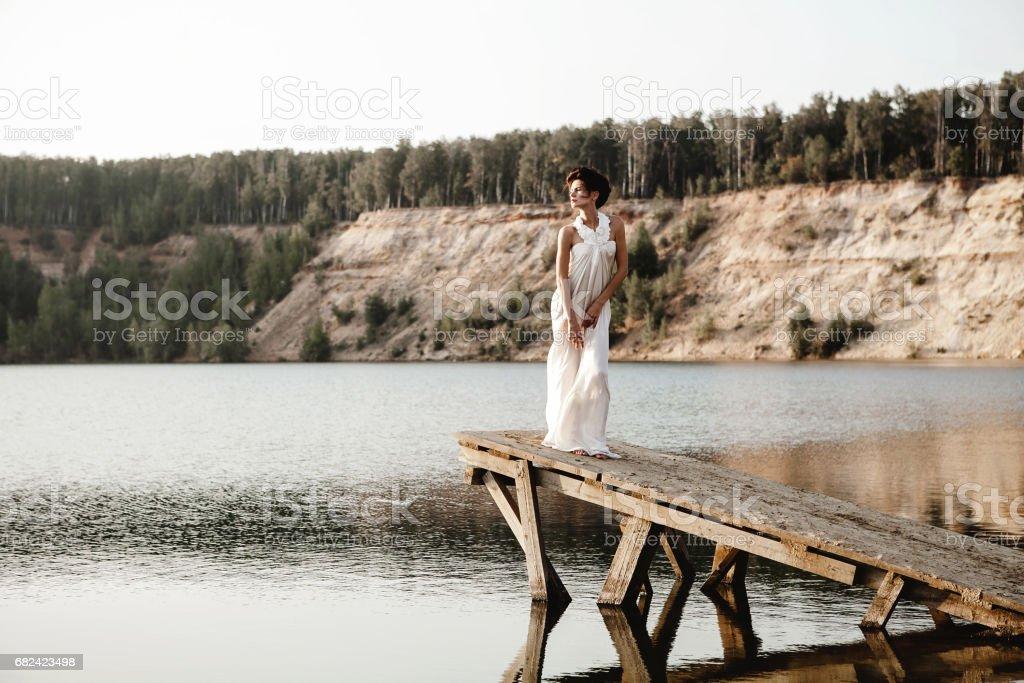 jeune fille debout sur une jetée sur un lac photo libre de droits