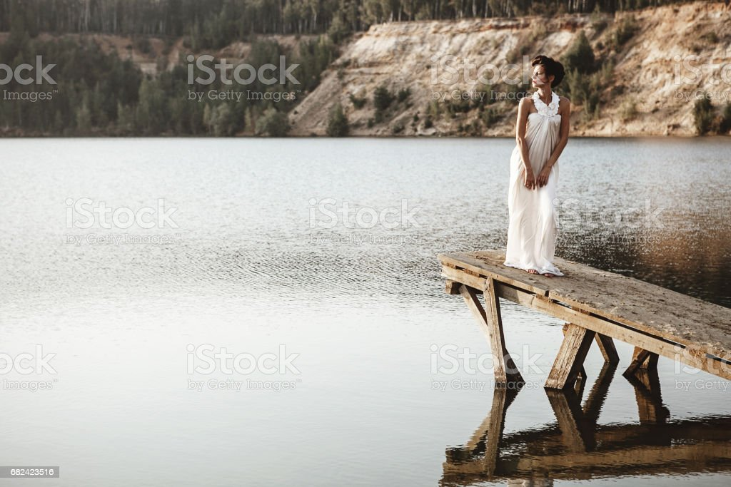 girl standing on a pier on a lake royalty-free stock photo