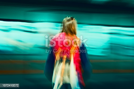 Abstract subway train in motion. Girl standing on a platform.