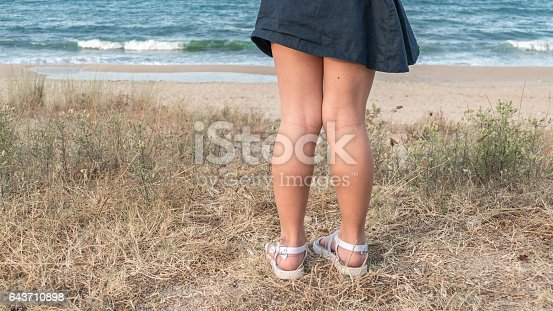 istock Girl standing on beach and looking at sea 643710898