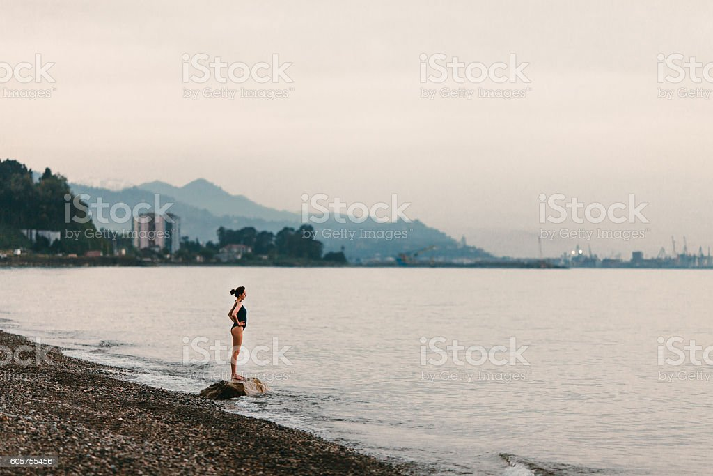 Girl standing on beach stock photo