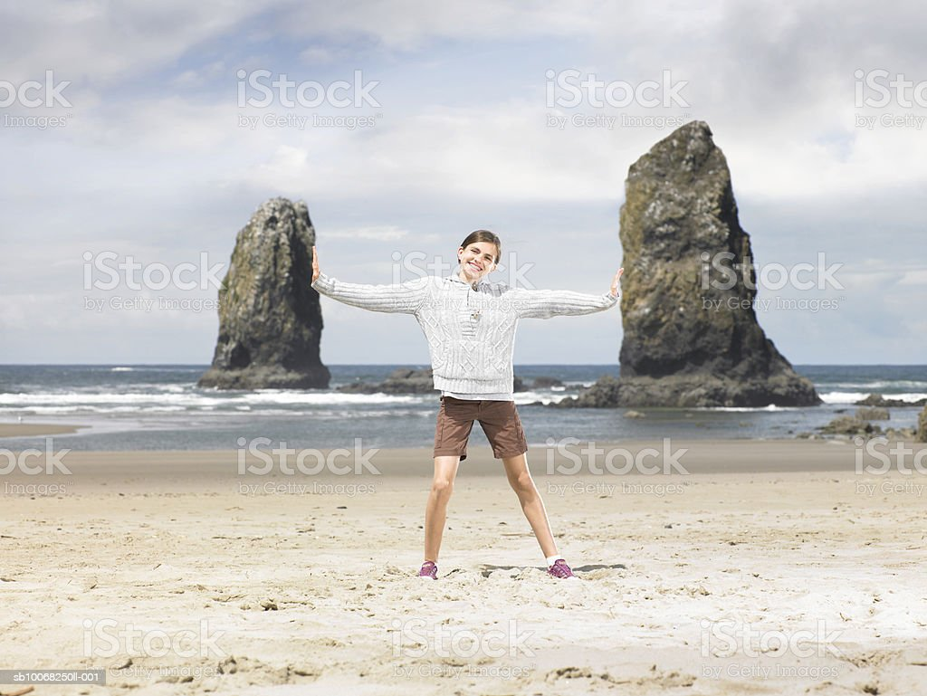 Girl (12-13) standing on beach  with arms outstretched, smiling, portrait 免版稅 stock photo