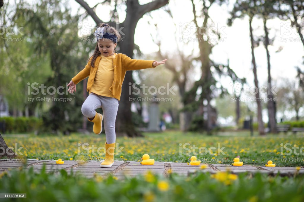 Little girl dancing and standing on one leg around a family of toy...
