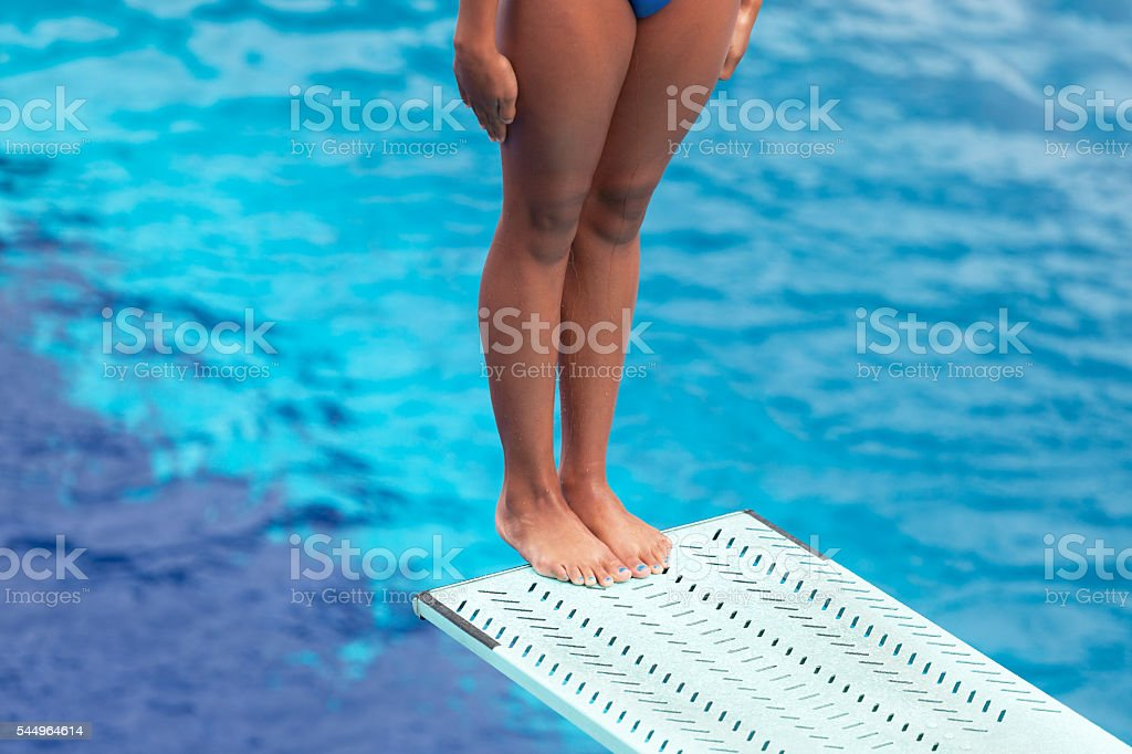 Girl standing on springboard, preparing to dive into swimming pool stock photo