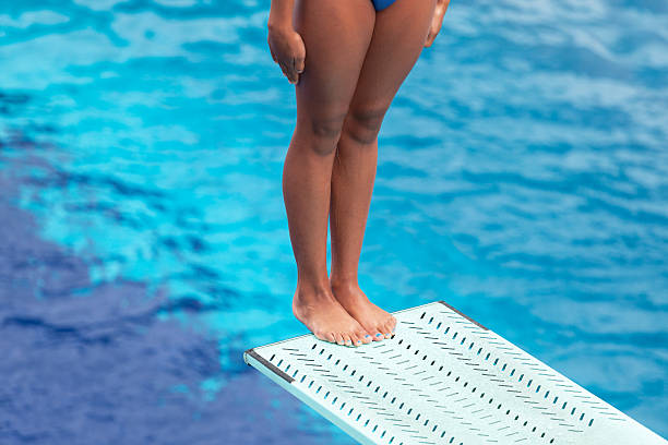 girl standing on springboard, preparing to dive into swimming pool - 다이빙 보드 뉴스 사진 이미지