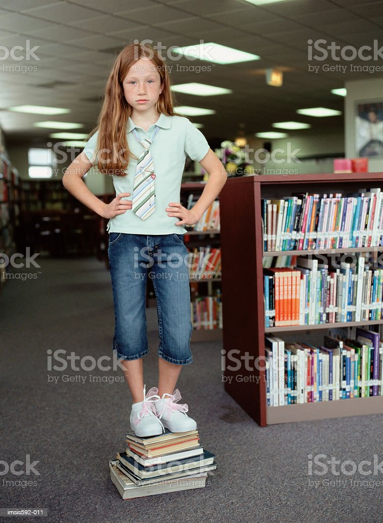 Girl standing on stack of books royalty free stockfoto