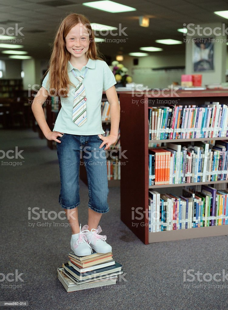 Girl standing on stack of books 免版稅 stock photo