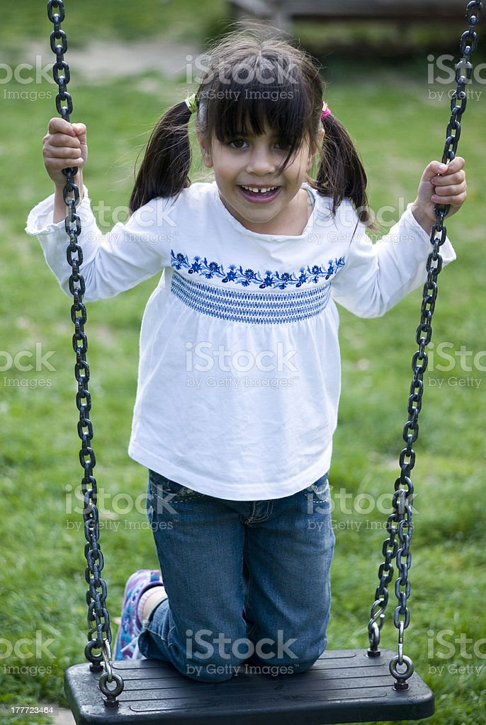 Girl standing on swing royalty-free stock photo