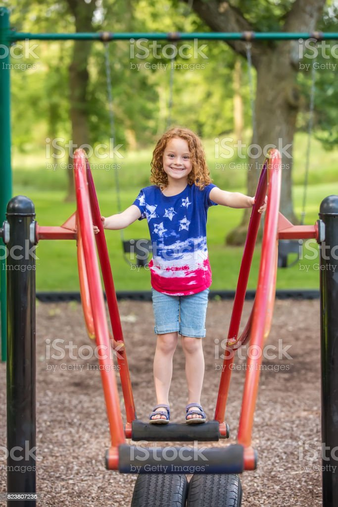 Girl Standing on Teeter Totter At Outdoor Playground stock photo