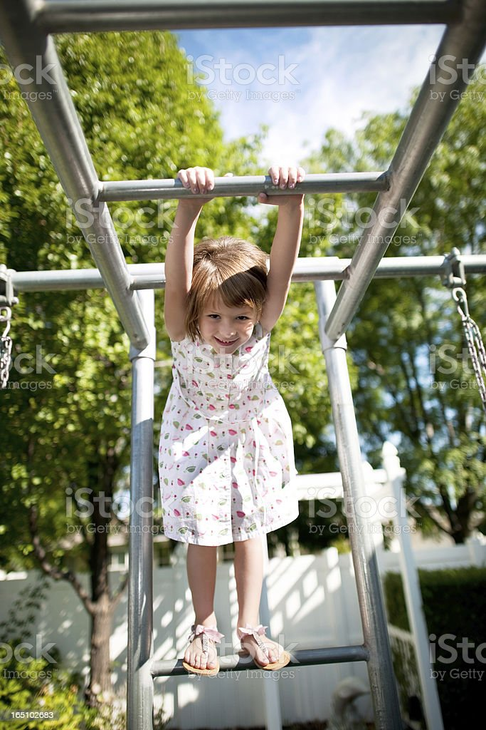 Girl Standing On The Monkey Bars stock photo