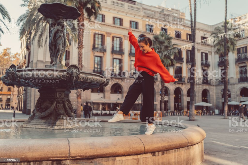 Girl standing on tip toes at the fountain stock photo