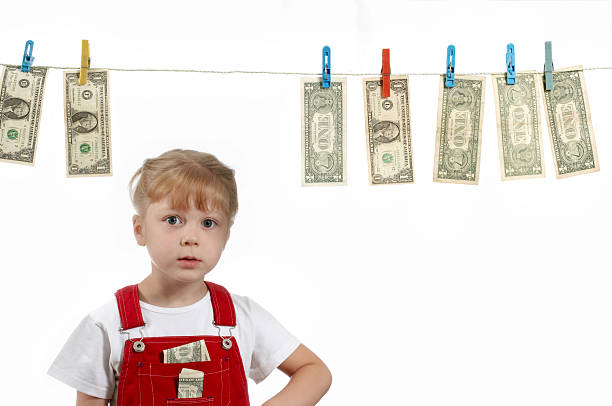 Girl standing under clothesline of dollar bills stock photo