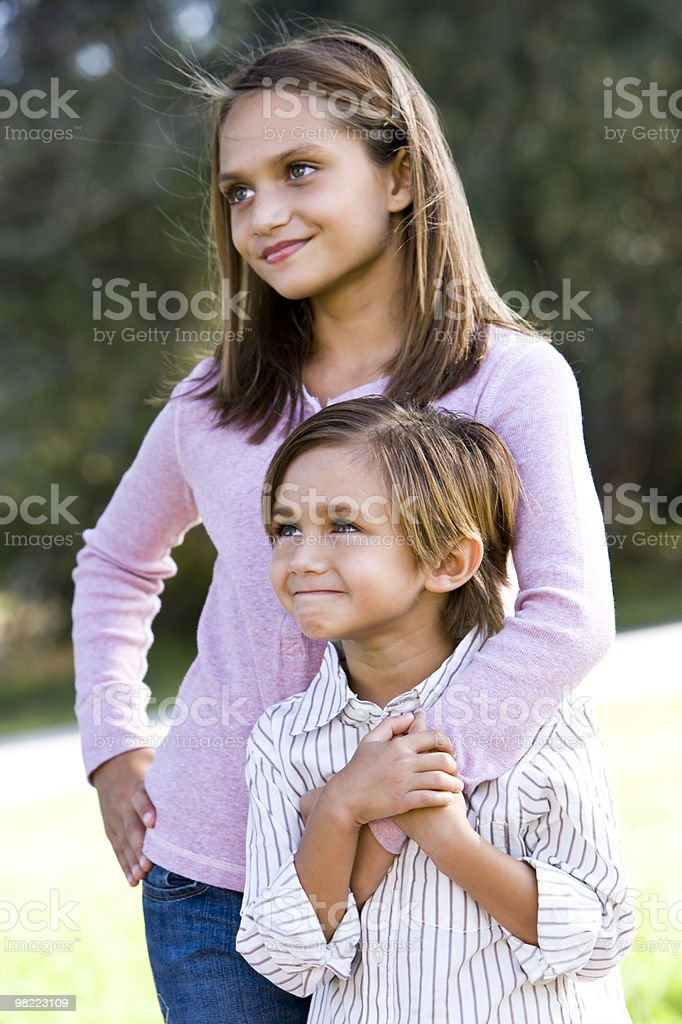 Girl standing with little brother outdoors stock photo